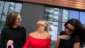 Trois femmes attirantes discutant leur jour d'achats Trois filles regardant des ventes au détail après l'achat dans le mail Linge banque de vidéos