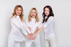 Trois femmes attirantes en portrait blanc sur le fond blanc Photo stock