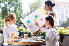 Trois femmes avec du charme discutant l'algorithme d'action en café Photos stock