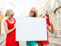 Trois femmes blondes heureuses avec le conseil blanc vide images stock