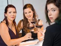Trois femmes buvant du vin rouge Image stock