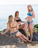 Trois femmes causant sur la plage sablonneuse Photos stock