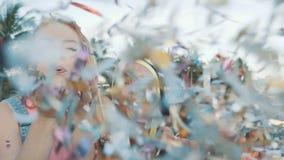 Trois femmes d'amis soufflant un pulvérisateur des confettis sur la plage au coucher du soleil banque de vidéos