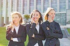 Trois femmes d'entreprise constituée en société se tenant et parlant sur le téléphone portable Photographie stock libre de droits