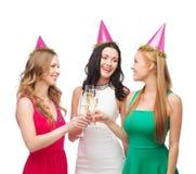 Trois femmes dans des chapeaux roses avec des verres de champagne Images stock