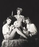 Trois femmes dans une grange découpant des potirons la nuit Photographie stock libre de droits