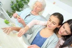 Trois femmes de générations faisant cuire au four ensemble Photographie stock