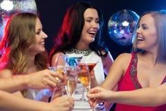 Trois femmes de sourire avec des cocktails dans le club Photographie stock libre de droits