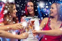 Trois femmes de sourire avec des cocktails dans le club Photos stock