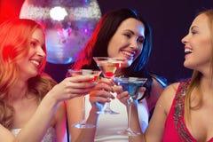 Trois femmes de sourire avec les cocktails et la boule de disco Photo libre de droits