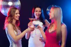 Trois femmes de sourire avec les cocktails et la boule de disco Image stock