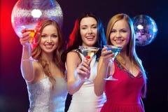 Trois femmes de sourire avec les cocktails et la boule de disco Image libre de droits