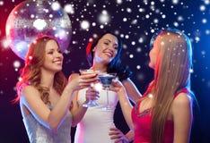 Trois femmes de sourire avec les cocktails et la boule de disco Images libres de droits