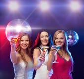 Trois femmes de sourire avec les cocktails et la boule de disco Images stock