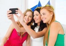 Trois femmes de sourire dans des chapeaux ayant l'amusement avec l'appareil-photo Image libre de droits