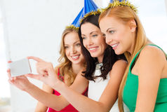 Trois femmes de sourire dans des chapeaux ayant l'amusement avec l'appareil-photo Photographie stock libre de droits