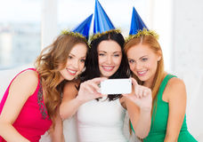 Trois femmes de sourire dans des chapeaux ayant l'amusement avec l'appareil-photo Photos stock