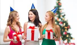 Trois femmes de sourire dans des chapeaux bleus avec des boîte-cadeau Images stock