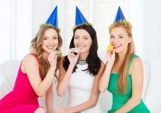 Trois femmes de sourire dans des chapeaux soufflant des klaxons de faveur image stock