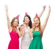 Trois femmes de sourire dans des chapeaux soufflant des klaxons de faveur Photo stock
