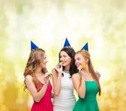 Trois femmes de sourire dans des chapeaux soufflant des klaxons de faveur photographie stock libre de droits