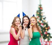 Trois femmes de sourire dans des chapeaux soufflant des klaxons de faveur images stock
