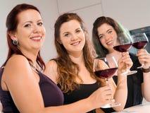 Trois femmes faisant un pain grillé avec du vin Photos stock