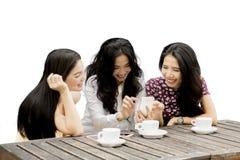 Trois femmes heureuses avec un téléphone portable Photographie stock