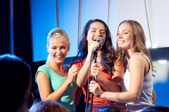 Trois femmes heureuses chantant sur l'étape de boîte de nuit Image libre de droits