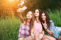 Trois femmes heureuses d'amis un selfie un jour d'étés en parc Photographie stock