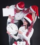 Trois femmes heureuses dans le costume de Santa Claus avec l'horloge, et le Chris image stock