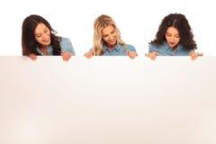 Trois femmes heureuses regardant vers le bas au grand conseil vide Photographie stock libre de droits