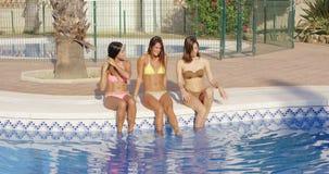 Trois femmes heureuses s'asseyant du côté d'une piscine banque de vidéos