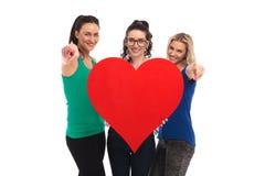 Trois femmes heureuses tenant un grand coeur rouge dirigeant des doigts Photographie stock