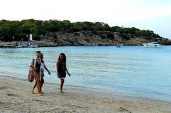 Trois femmes marchant à côté du bord de la mer sur la plage célèbre et touristique de l'île d'Ibiza photographie stock libre de droits