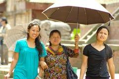 Trois femmes marchent dans la place de Durbar et protègent la forme le soleil avec Photographie stock libre de droits