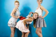 Trois femmes montrant des chaussures de talons hauts Photo stock