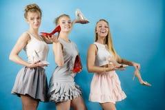 Trois femmes montrant des chaussures de talons hauts Photographie stock