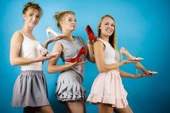 Trois femmes montrant des chaussures de talons hauts Image libre de droits