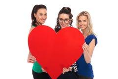 Trois femmes occasionnelles de sourire tenant un grand coeur rouge Photo libre de droits