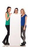 Trois femmes occasionnelles heureuses présent un grand conseil vide Image libre de droits
