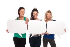 Trois femmes occasionnelles heureuses tenant le discours vide bouillonne des conseils Images libres de droits