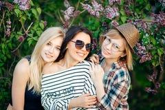 Trois femmes occasionnelles sûres se tenant au parc et regardant l'appareil-photo Photos stock