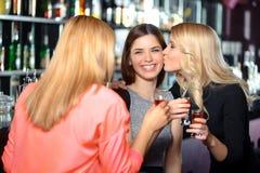 Trois femmes ont une boisson dans la barre Photo stock