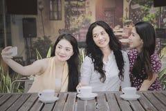 Trois femmes prenant la photo dans le café Image stock