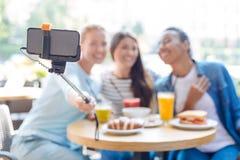 Trois femmes prenant un selfie ensemble dans le restaurant Image libre de droits