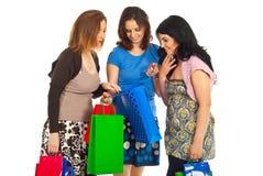 Trois femmes regardant dans le sac à provisions Photo stock