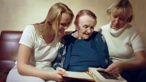 Trois femmes regardant par les archives de famille banque de vidéos