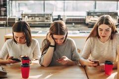 Trois femmes s'asseyant au café utilisant les téléphones intelligents Image stock