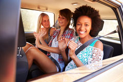 Trois femmes s'asseyant dans Seat arrière de voiture sur le voyage par la route Photos libres de droits